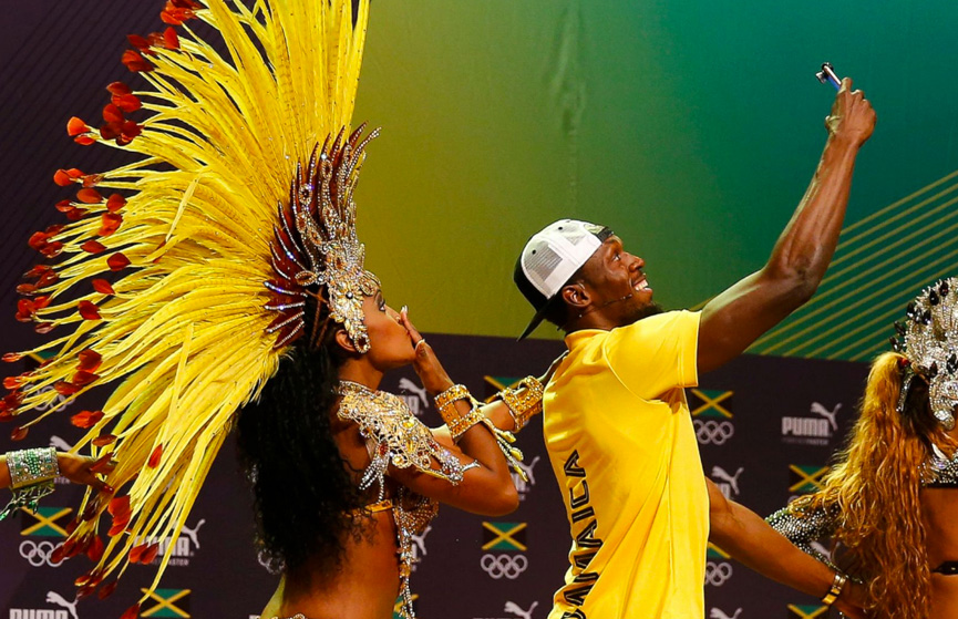 Jamaican-track-star-Usain-Bolt-with-Brazilian-samba-dancers-at-a-press-conference