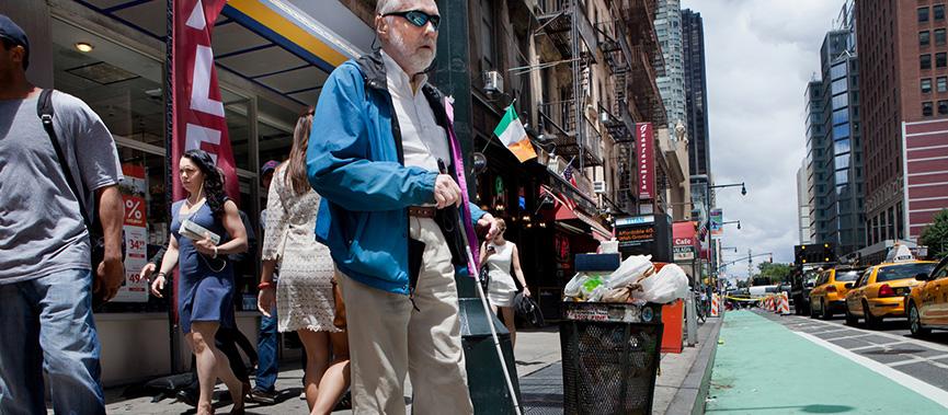 #PraCegoVer: cidade cheia de pessoas e movimento. No centro da imagem, um senhor cego com bengala aguarda para atravessar a rua.